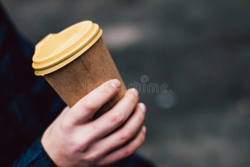 Una taza de café caliente de papel en la mano masculina imagen de archivo libre de regalías