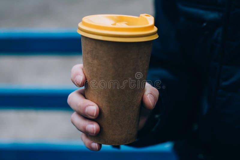 Una taza de café caliente de papel en la mano masculina amarillo imagen de archivo