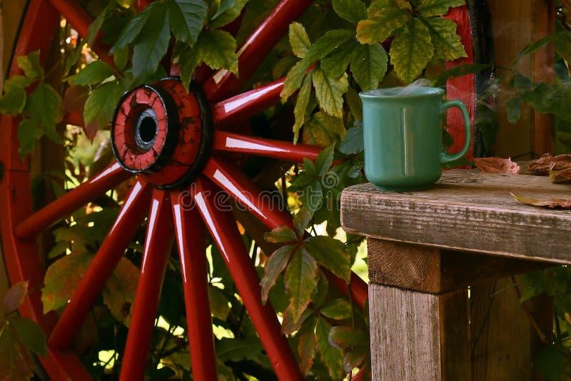 Una taza de café caliente y humeante en un banco de madera, con una vieja rueda de madera foto de archivo