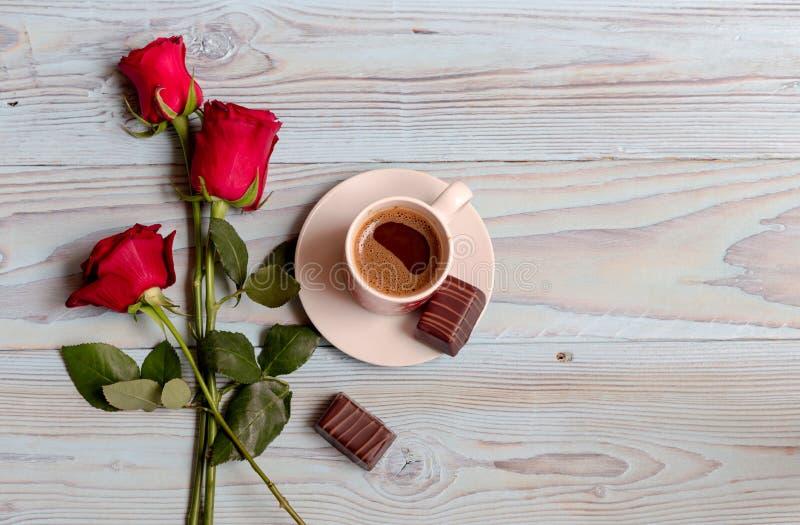 Una taza de café, de caramelo y de rosas foto de archivo libre de regalías