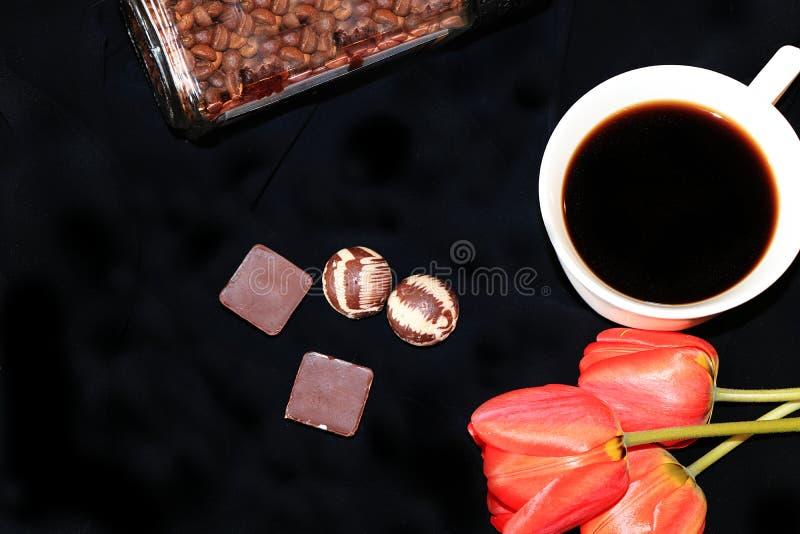 Una taza de café, de chocolate y de tulipanes en un primer negro del fondo, foco selectivo fotografía de archivo libre de regalías