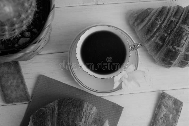 Una taza de café con el café express, cruasanes, galletas, cactus en la cesta, orquídea en un fondo de madera, blanco y negro fotos de archivo libres de regalías