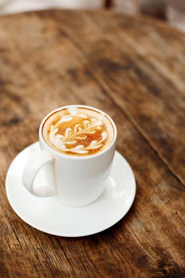 Una taza de café con el modelo de la hoja imagen de archivo libre de regalías