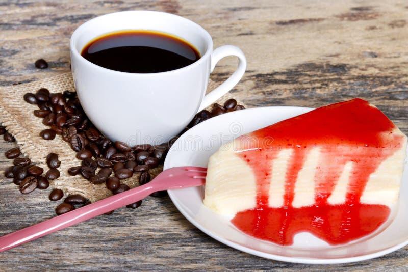 Una taza de café con el pastel de queso cortado imagenes de archivo