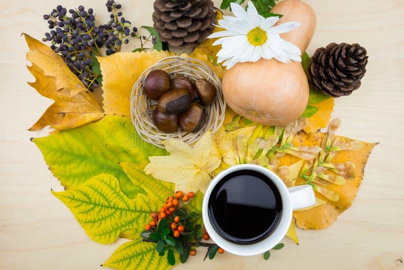 Una taza de café con el ramo de hojas, de bayas y de semillas de otoño imagen de archivo