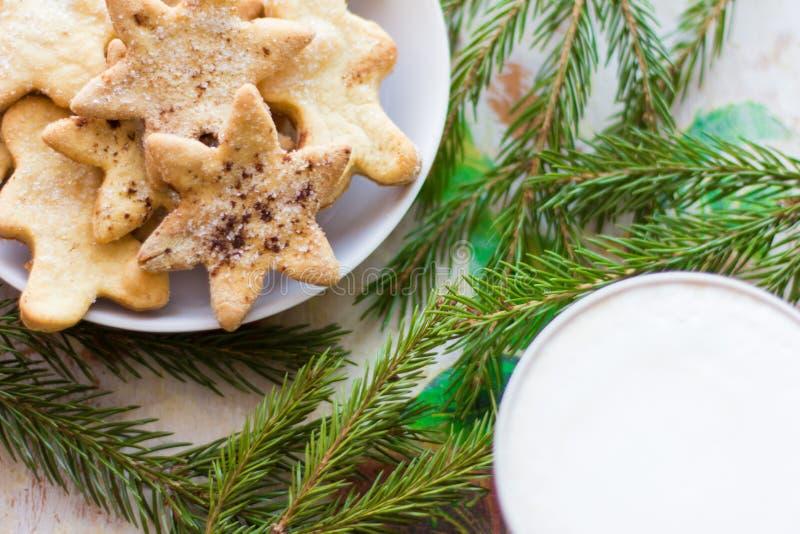 Una taza de café con una espuma gruesa y de galletas de la Navidad con el azúcar y el canela foto de archivo