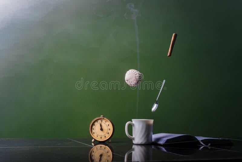 Una taza de café con la melcocha y el canela del vuelo foto de archivo