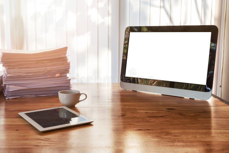 Una taza de café con la tableta y de materiales de oficina en el escritorio de oficina Tabla de madera con los materiales de ofic imágenes de archivo libres de regalías