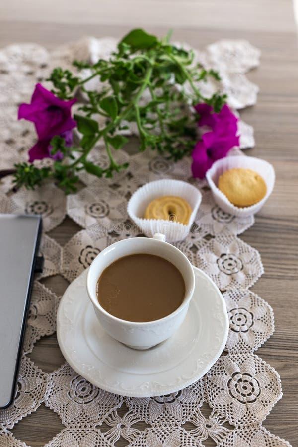 Una taza de café con leche y galletas imagen de archivo libre de regalías