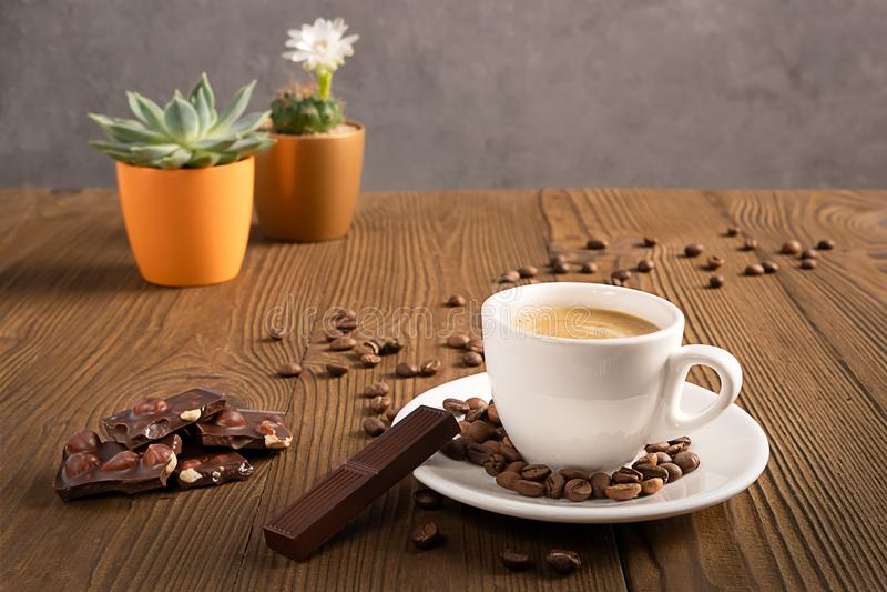 Una taza de café con los granos y el chocolate de café en una tabla de madera con las macetas coloridas, foco selectivo imagen de archivo libre de regalías