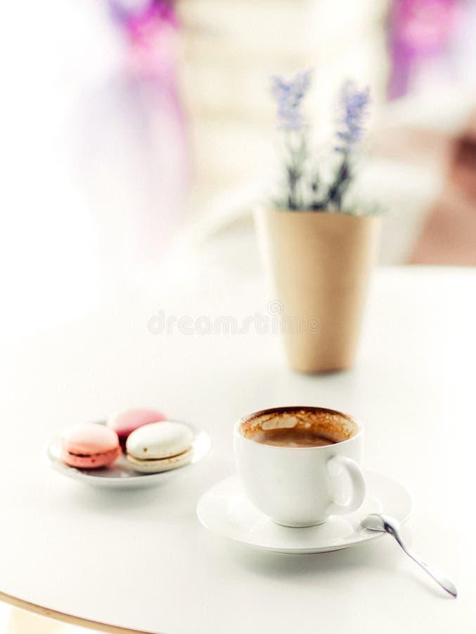 Una taza de café con los macarrones y la lavanda en la tabla foto de archivo libre de regalías