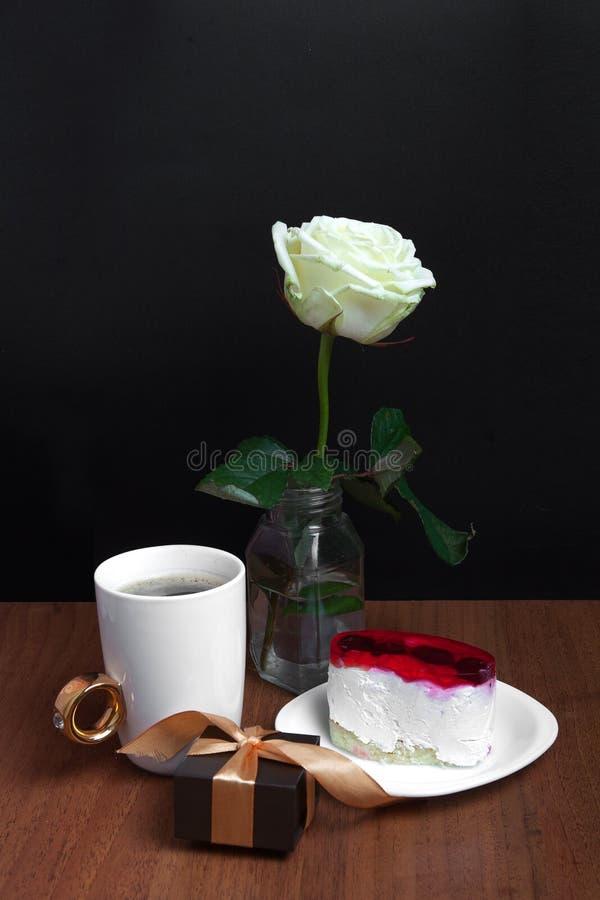 Una taza de café con una torta y una rosa en un fondo negro Día del `s de la tarjeta del día de San Valentín imagen de archivo libre de regalías