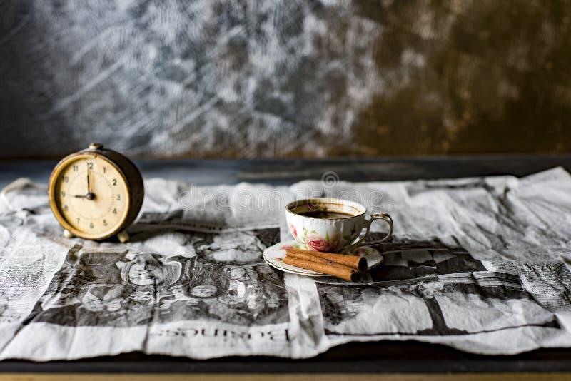 una taza de café con un despertador en un periódico viejo fotos de archivo libres de regalías