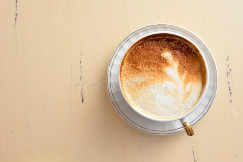 Una taza de café con un modelo de la hoja en una tabla del vintage imagenes de archivo