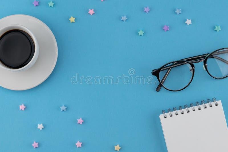 Una taza de café, de cuaderno en blanco y de lentes fotos de archivo