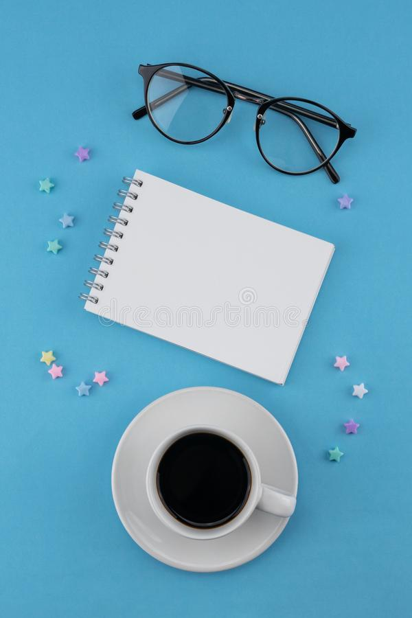 Una taza de café, de cuaderno en blanco y de lentes foto de archivo libre de regalías