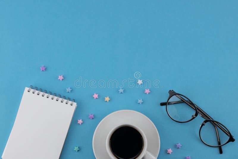 Una taza de café, de cuaderno en blanco y de lentes fotografía de archivo libre de regalías