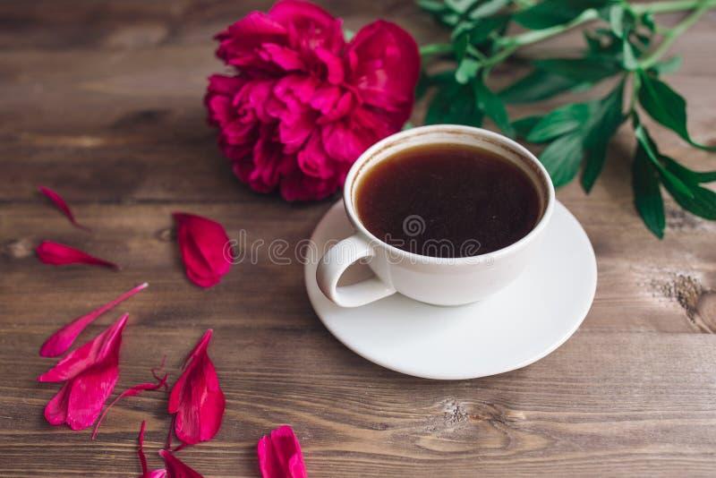 Una taza de café, de peonías rojas modelo y de caja de regalo en fondo de madera Buenos días foto de archivo libre de regalías