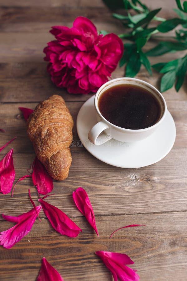 Una taza de café, de peonías rojas modelo y de cruasán en fondo de madera Buenos días ` S de las mujeres o fondo del día del ` s  imágenes de archivo libres de regalías
