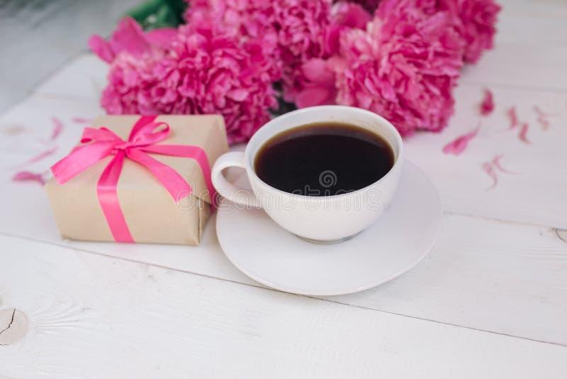 Una taza de café, de peonías rosadas modelo y de caja de regalo en fondo de madera foto de archivo