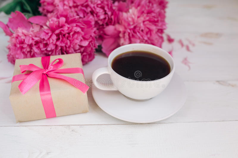 Una taza de café, de peonías rosadas modelo y de caja de regalo en fondo de madera fotos de archivo