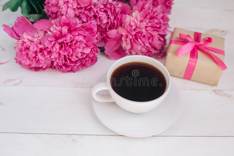 Una taza de café, de peonías rosadas modelo y de caja de regalo en fondo de madera fotografía de archivo libre de regalías