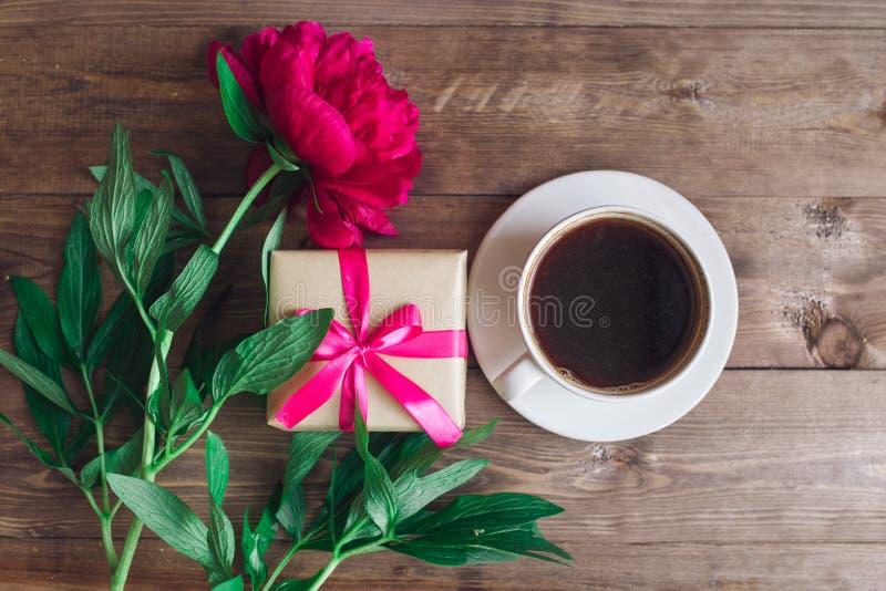 Una taza de café, de peonías rosadas modelo y de caja de regalo en fondo de madera Buenos días ` S de las mujeres o fondo del día imagen de archivo libre de regalías