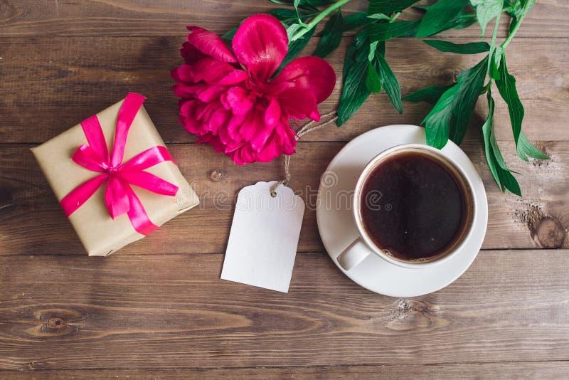 Una taza de café, de peonías rosadas modelo y de caja de regalo en fondo de madera Buenos días ` S de las mujeres o fondo del día fotos de archivo libres de regalías