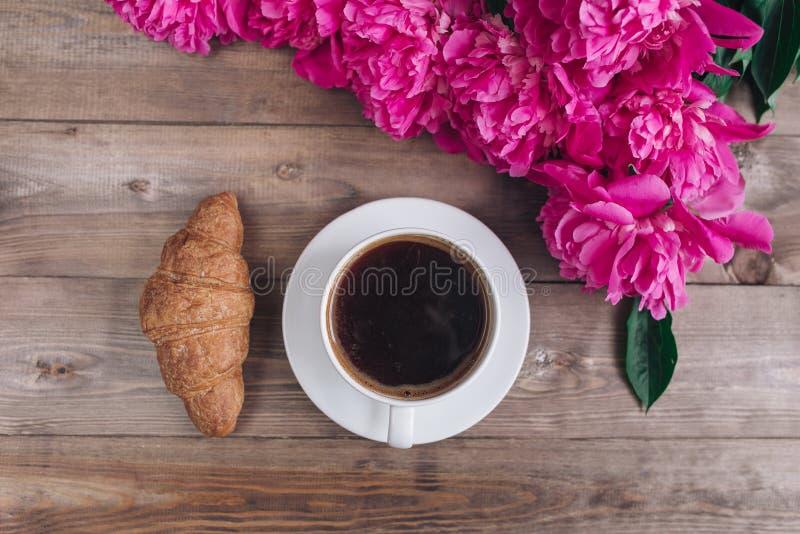 Una taza de café, de peonías rosadas modelo y de cruasán en fondo de madera Buenos días ` S de las mujeres o fondo del día del `  imagen de archivo