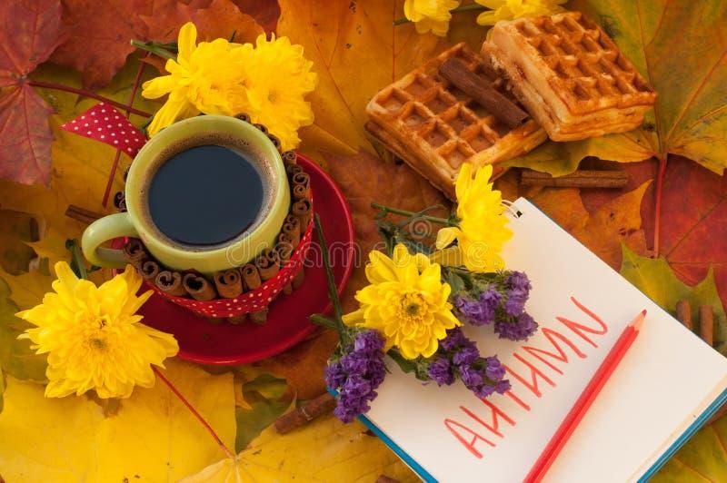 Una taza de café, de un cuaderno, de galletas hechas en casa, de hojas de arce, de flores del otoño y de palillos de canela imágenes de archivo libres de regalías