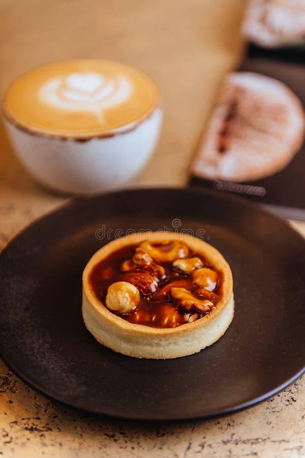 Una taza de café del latte, del capuchino o del café express con la leche puesta en una tabla de madera imagen de archivo