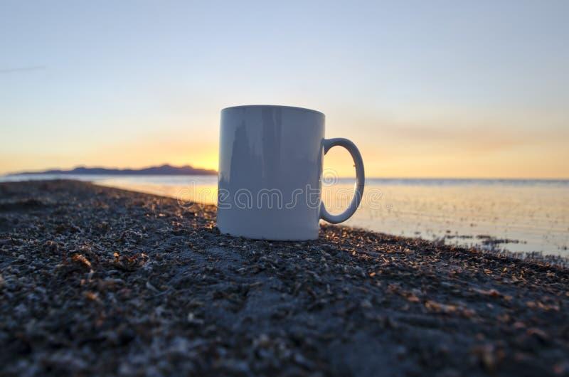 Una taza de café en blanco a solas en el shorline imagen de archivo