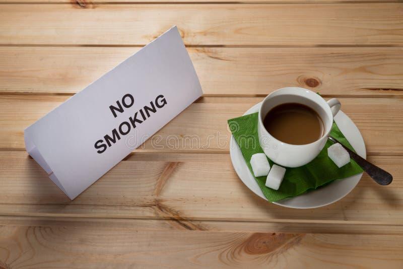 Una taza de café en una tabla de madera con una nota de no fumadores foto de archivo libre de regalías