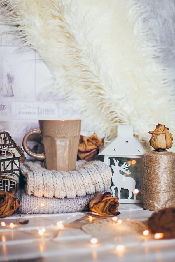 Una taza de café en un atmoshere relajante acogedor del balneario en el humor con la linterna de las velas, cosas hechas punto, l imágenes de archivo libres de regalías