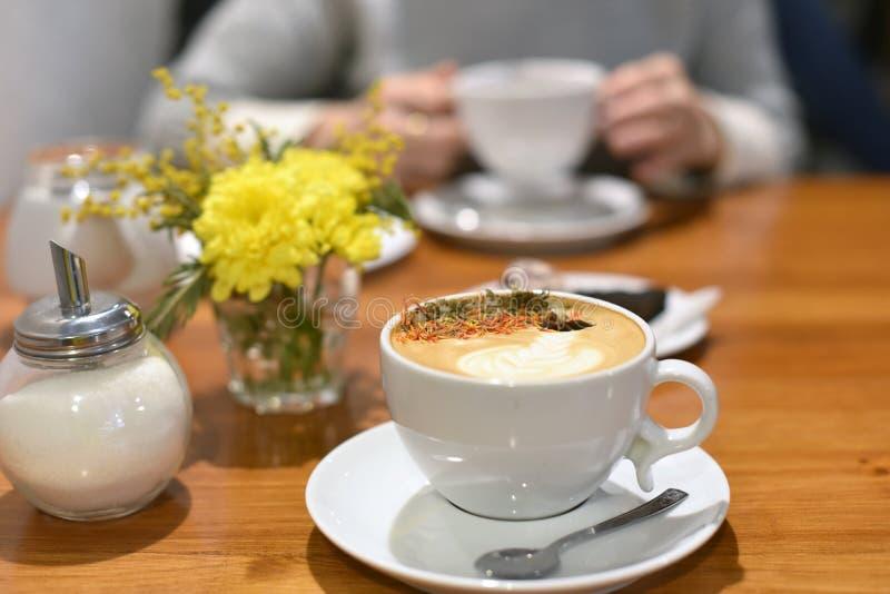 Una taza de café en una tabla de madera y un par del ` s de la mujer da sostener otra taza en el fondo fotos de archivo libres de regalías