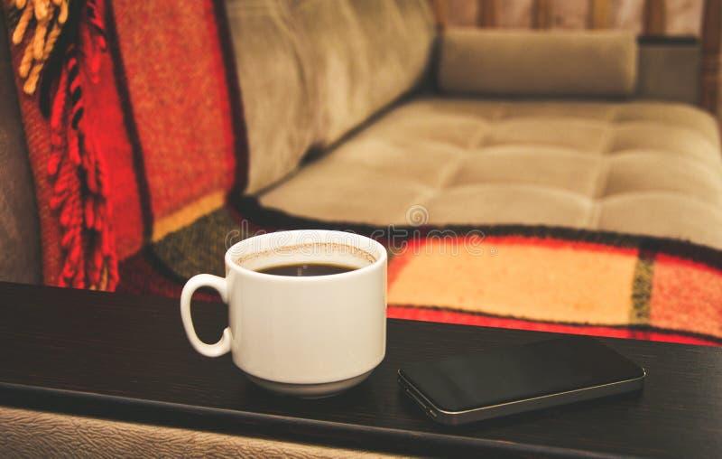 Una taza de café está en la tabla del sofá, es después un teléfono móvil, comodidad casera fotografía de archivo