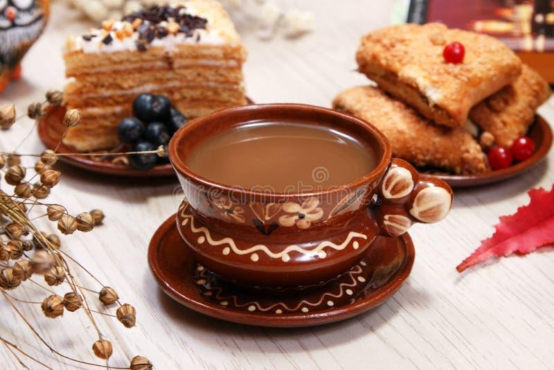 Una taza de café, de galletas de la fruta, de torta y de una figura de un gato rojo en la tabla Fondo blanco Planta del lino seca fotos de archivo
