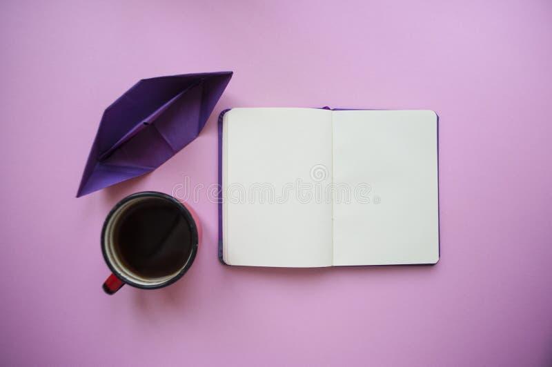 Una taza de café, la nave del papel y un cuaderno encendido gruñen el fondo fotografía de archivo libre de regalías