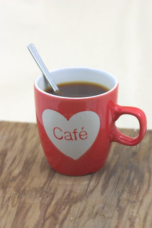 Una taza de café roja con un corazón en una tabla de madera imagenes de archivo