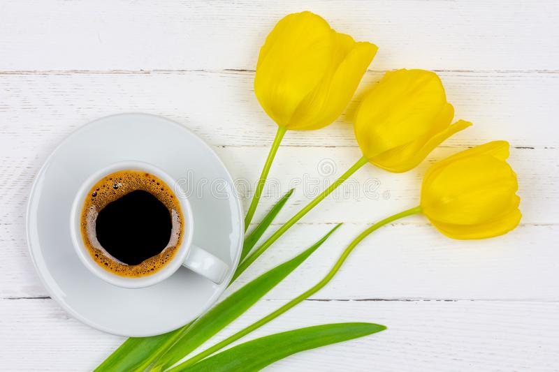 Una taza de café sólo en un platillo y una flor amarilla del tulipán tres en un primer de madera blanco del fondo, visión superio foto de archivo