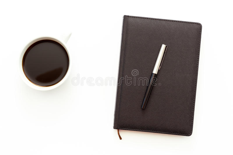 Una taza de café sólo y de un planificador del día con la pluma en el fondo blanco Concepto mínimo del negocio de la endecha plan fotos de archivo
