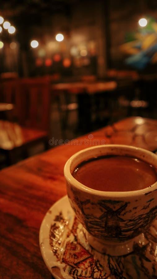 Una taza de café sirvió en una tabla de madera con una cafetería tranquila del ambiente foto de archivo