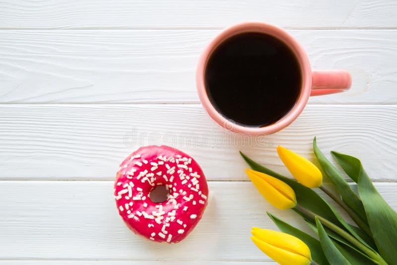 Una taza de caf? y de bu?uelo en la tabla y la flor blancas, concepto del cumplea?os Concepto del saludo fotos de archivo