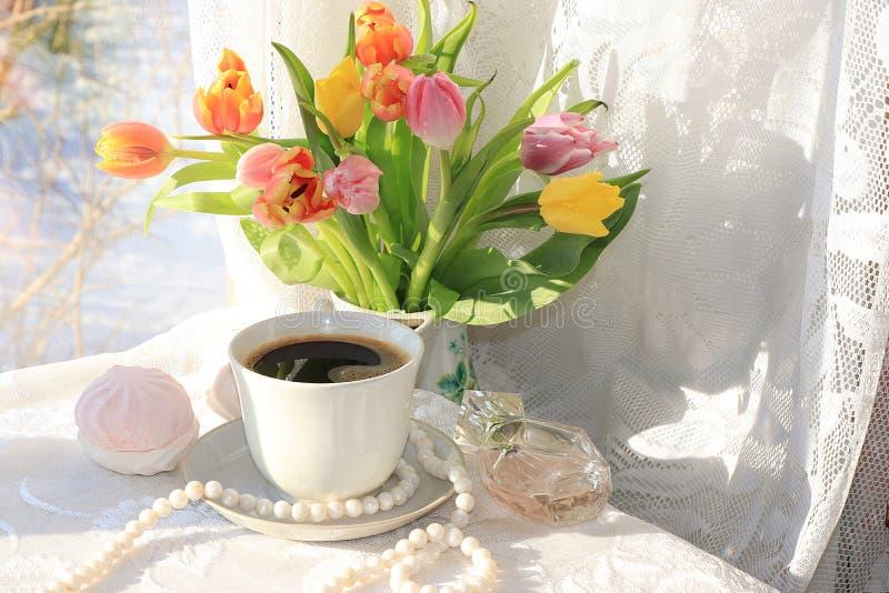 Una taza de café y de flores en un fondo ligero foto de archivo