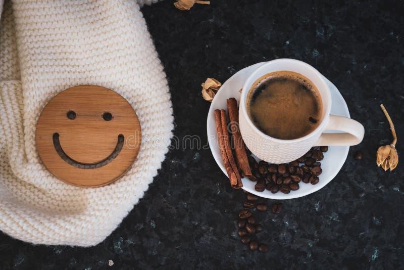 Una taza de caf? es la llave a un buen humor Smiley de madera en un fondo oscuro, negro, de textura En la tabla hay un blanco, imagen de archivo libre de regalías