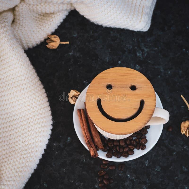 Una taza de caf? es la llave a un buen humor Smiley de madera en un fondo oscuro, negro, de textura En la tabla hay un blanco, foto de archivo libre de regalías