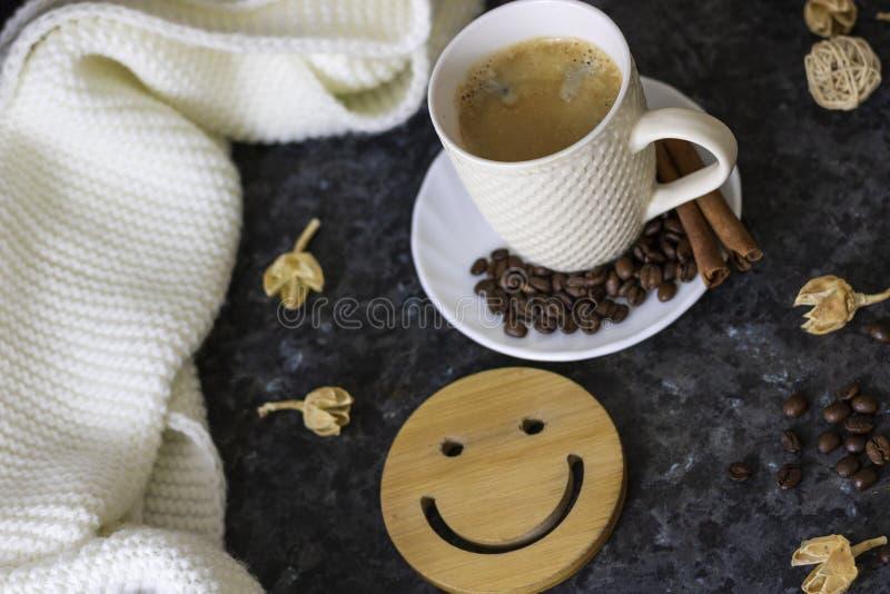 Una taza de caf? es la llave a un buen humor Smiley de madera en un fondo oscuro, negro, de textura En la tabla hay un blanco, imagen de archivo