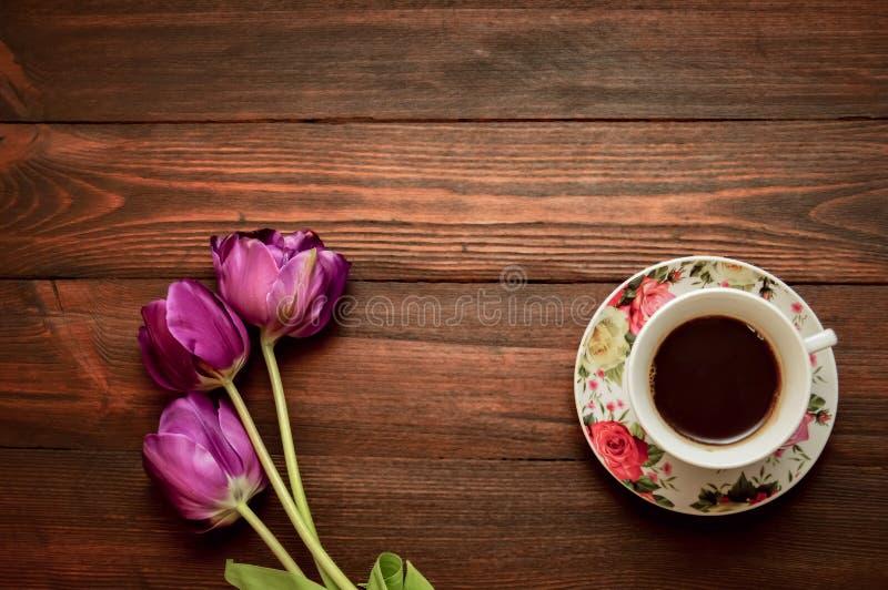Una taza de caf? o de t? en un platillo se coloca en un fondo de madera, los tulipanes p?rpuras miente despu?s foto de archivo
