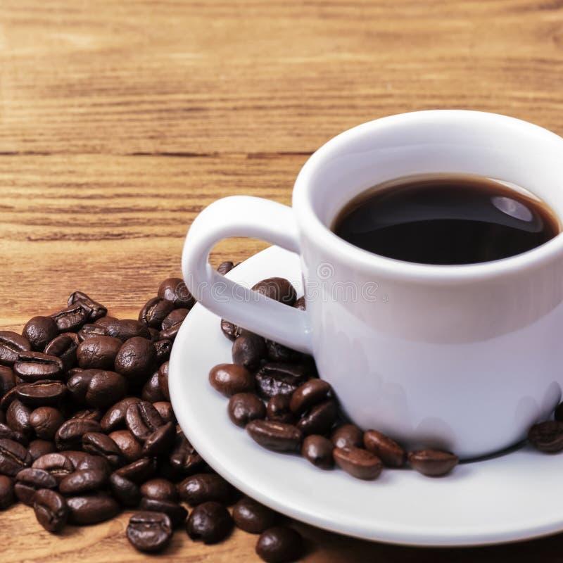 Una taza de caf? y de granos de caf? dispersados disposici?n Endecha plana Grano de caf? foto de archivo