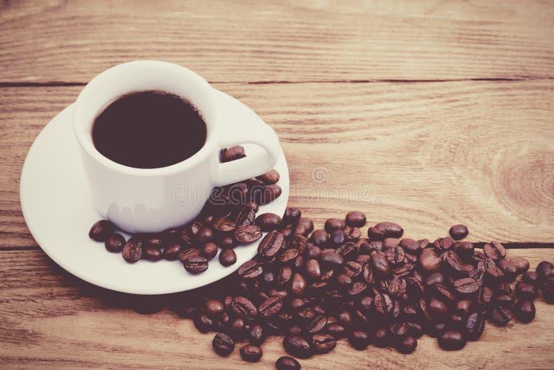 Una taza de caf? y de granos de caf? dispersados disposici?n Endecha plana Grano de caf? fotos de archivo
